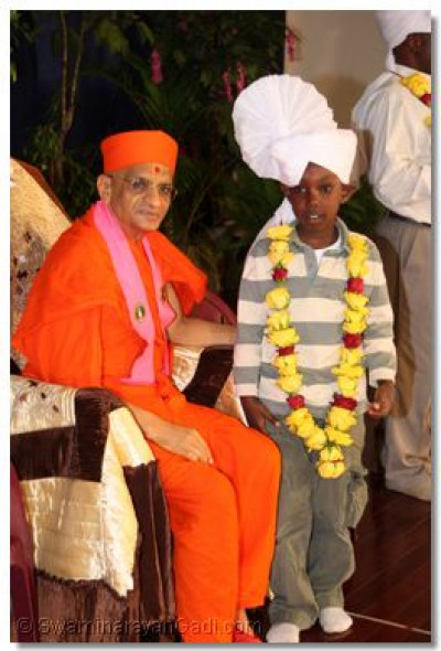 Acharya Swamishree blesses the son of the chief guest