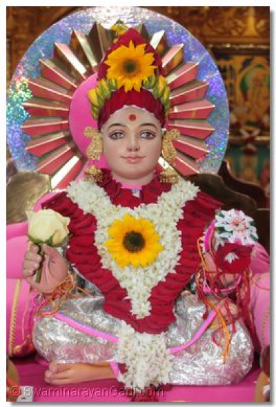Shree Ghanshyam Maharaj adorned with a flower chadar and mugat