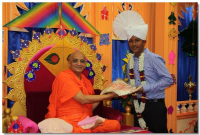 Acharya Swamishree presents a paagh, shawl and flower garland to the parayan benefactor