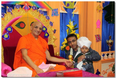 Acharya Swamishree presents a paagh and flower garland to the parayan benefactor