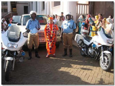 Police escort officers with Acharya Swamishree