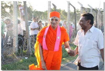 Acharya Swamishree marches past hundreds of devotees gathered at the airport