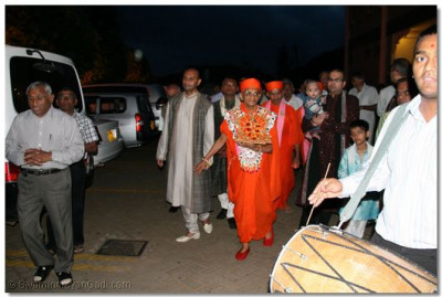 Disciples lead His Divine Holiness Acharya Swamishree and Shree Harikrishna Maharaj through Shree Swaminarayan Temple Nairobi as dhol players perform a welcoming repertoire