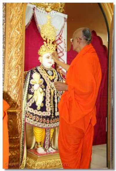 His Divine Holiness Acharya Swamishree lovingly applies chandlo to Lord Shree Swaminarayan