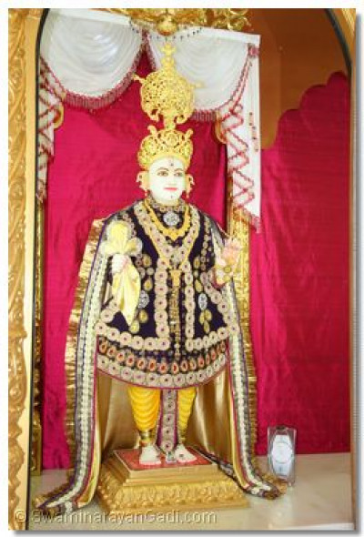 Divine darshan of Lord Shree Swaminarayan adorned in beautifully decorated navy blue garments, a golden shawl and a magnificent golden crown