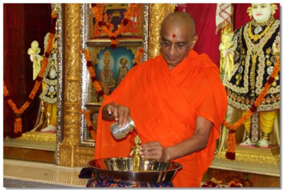 His Divine Holiness Acharya Swamishree bathes Shree Harikrishna Maharaj with each of the five nectars (saffron water)
