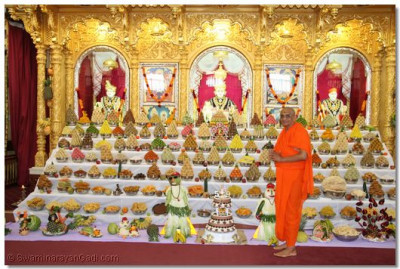 His Divine Holiness Acharya Swamishree offers a slice of the Anniversary cake to Lord Shree SwaminarayanBapa Swamibapa