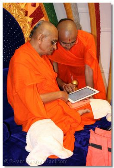 His Divine Holiness Acharya Swamishree gives darshan with the newly released Shree Harignanamrut ebook publication