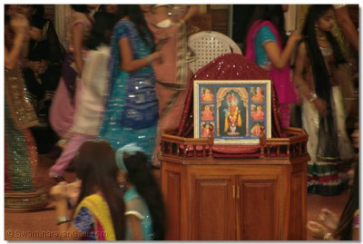 The divine form of Lord Shree SwaminarayanBapa Swamibapa is placed at the centre as disciples play raas
