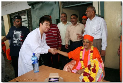 A Chinese worker at the yard is fortunate to get the darshan and blessings from Acharya Swamishree