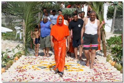 Acharya Swamishree along with his haribhakto make their way onto the beach