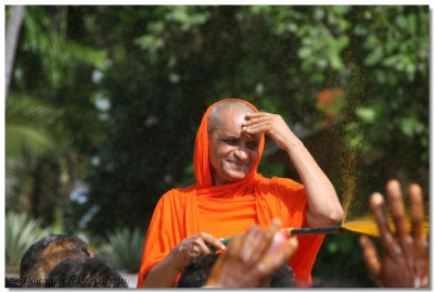 Devotees get the chance to be showered in coloured water by Acharya Swamishree