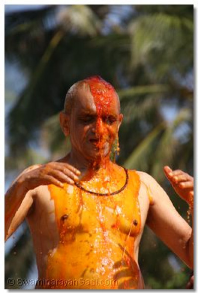 Divine darshan of Acharya Swamishree as he is covered in coloured water