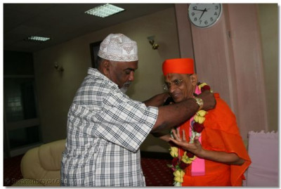 The Mayor of Mombasa presents Acharya Swamishree with a flower garland