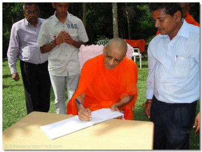 HDH Acharya Swamishree signs a visitor's book