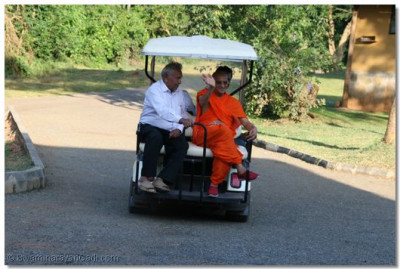 Acharya Swamishree on the golf cart taking a tour of the lodge