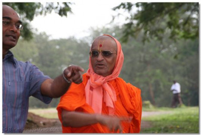 Devotee showing Acharya Swamishree the site where an elephant was sighted the previous night