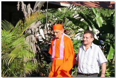 HDH Acharya Swamishree being escorted by a disciple
