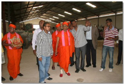 Acharya Swamishree being guided by the disciples during a padharamani at the plastic tank manufacturing factory