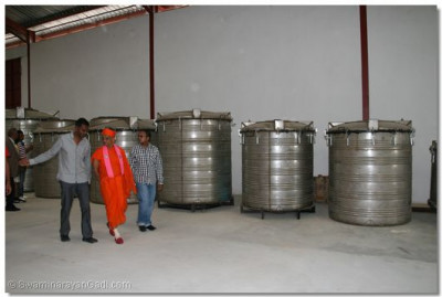 Devotee showing Acharya Swamishree the different moulds for the tanks being produced at the factory