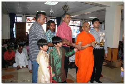 Acharya Swamishree and disciples performing arti to Lord Swaminarayan