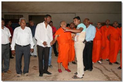 A member of the plant explaining to Acharya Swamishree how the stock piling is carried out