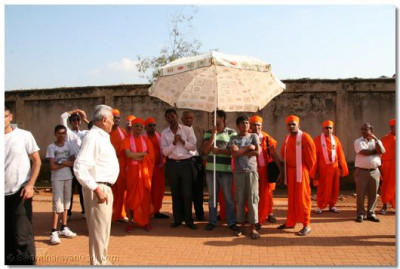 Acharya Swamishree and devotees gathered to see the cranes whilst in operation