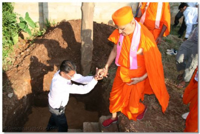 Devotee guiding Acharya Swamishree for the stone laying ceremony