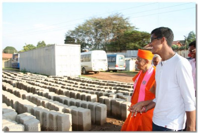 Devotee showing Acharya Swamishree the parcel of land and explaining the future plans to be carried out at the site