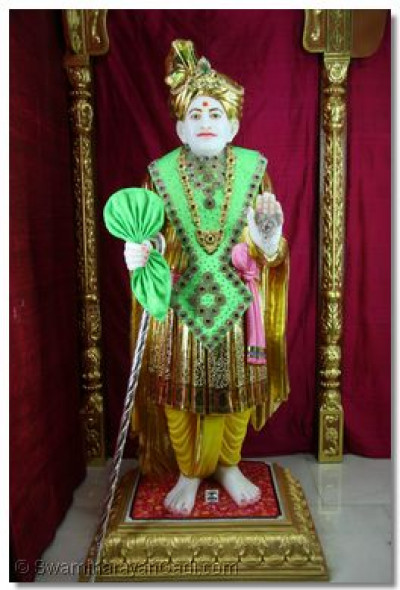 Jeevanpran Abji Bapashree in a gem-stone embedded green garland