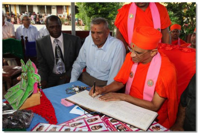 Acharya Swamishree signs the visitor's book at the school