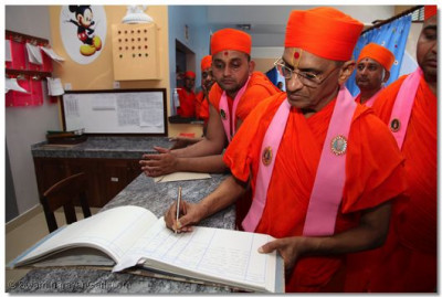 Acharya Swamishree signs the visitor's book at the hospital