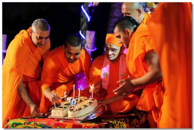 Acharya Swamishree and sants light the cake candles