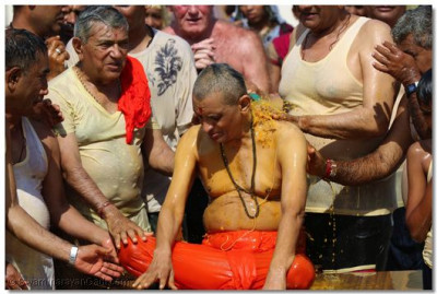 Devotees get a chance to shower coloured water on Acharya Swamishree