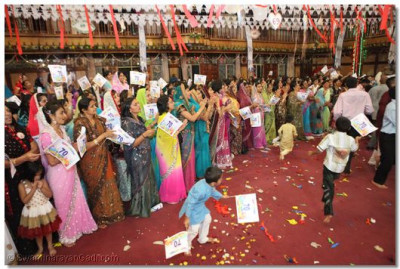Devotees wave flags during samuh raas