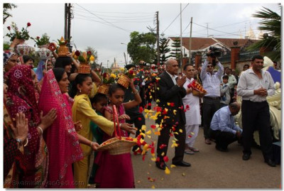 Devotees welcome Acharya Swamishree with flower petals