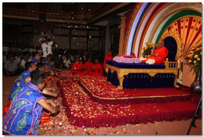 Devotees shower Acharya Swamishree with flower petals during the dance