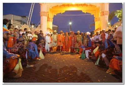 Acharya Swamishree arrives at the temple gate as devotees welcome Him with a dance