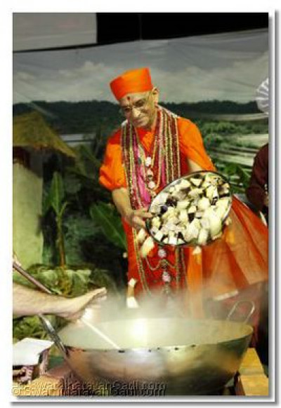 HDH Acharya Swamishree pours cut aubergine into the cooking pan