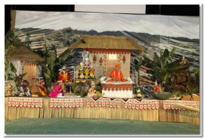 Acharya Swamishree on the stage with scenic background