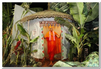 Acharya swamishree at the entrance of a straw hut