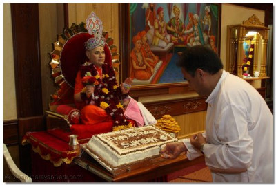 Poojari cuts the cake on behalf of all the devotees.
