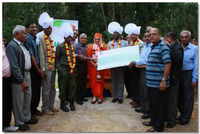 "Acharya Swamishree and the comittee members offer a cheque to the "" Friends of Karura Forest"""