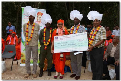 "Acharya Swamishree offers a cheque to the "" Friends of Karura Forest"""