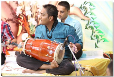 "A devotee playing the ""dholak""."