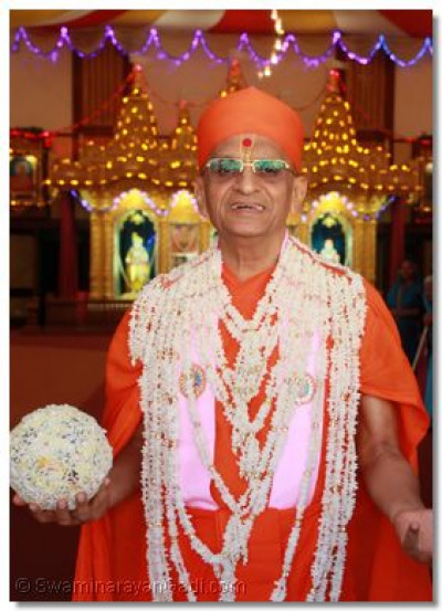 Divine darshan of Acharya Swamishree adorned in a garland made of puffed rice