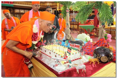 Acharya Swamishree blows the candles on the cake.