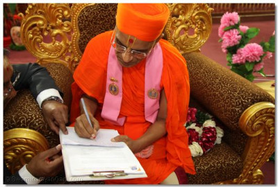 Acharya Swamishree passes his message to the guest.