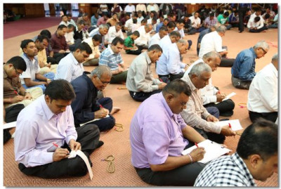 Devotees writing mantra.
