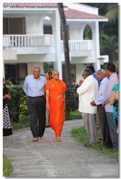 Acharya Swamishree goes for a walk in the beach.